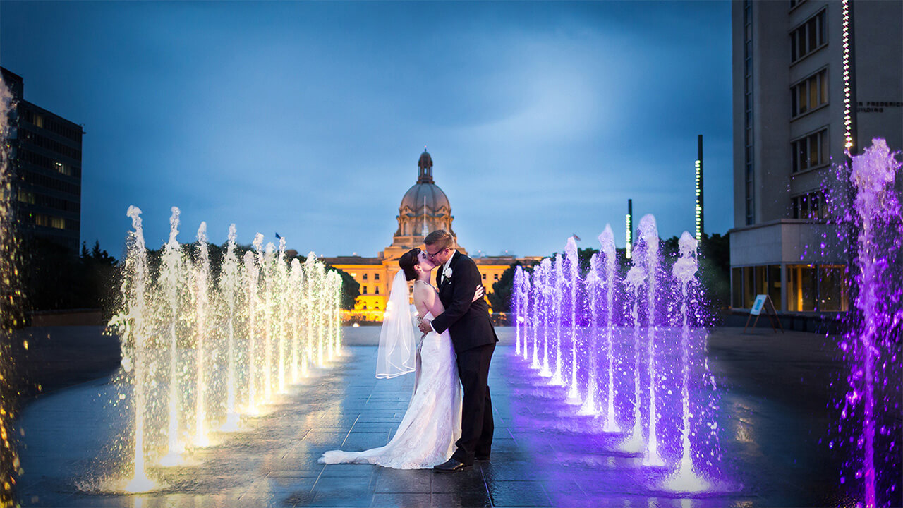 Edmonton Wedding Photographer with couple at fountains at Alberta Legislature